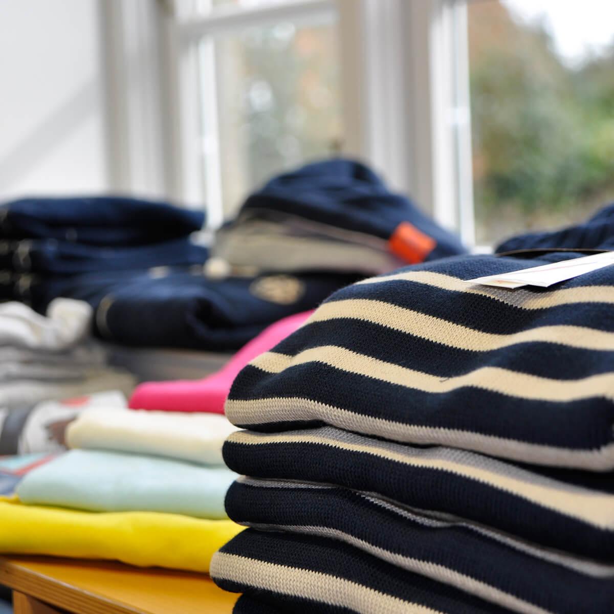 Verschiedene Kleidungsstücke vor einem Fenster