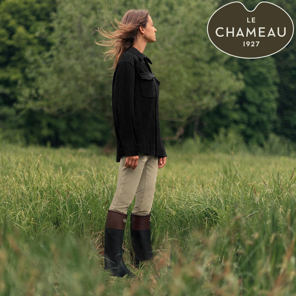 Frau auf einer Wiese mit Le Chameau Stiefeln